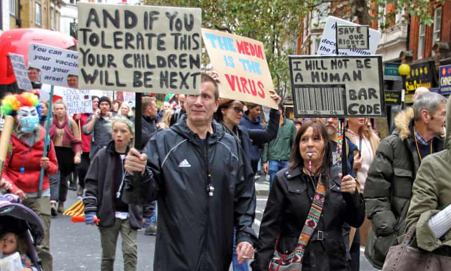 Demonstrators march through Leicester Square holding placards