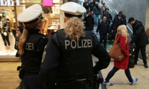 Police officers patrolling and watching over travellers inside Cologne Main Station.