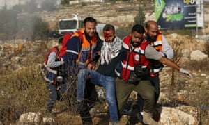 Palestinian paramedics help a demonstrator who was wounded by Israeli security forces during a demonstration against the Israeli offensive on Gaza.