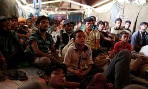 Indians watch TV under a bridge in New Delhi.
