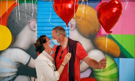 A couple kiss wearing masks at an art exhibition to thank medical staff at Pitié-Salpêtrière hospital in Paris.
