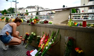 A girl lays flowers and candles outside the Olympia shopping centre on Saturday morning.