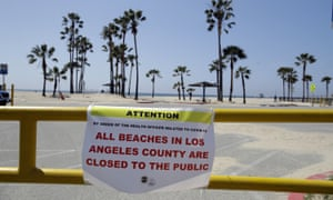 a closure sign is placed at the entrance of a beach front parking lot in the Venice beach section of Los Angeles