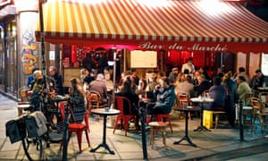 People enjoy a drink in a cafe terrace as French President Emmanuel Macron deploys curfew amid accelerating coronavirus pandemic.