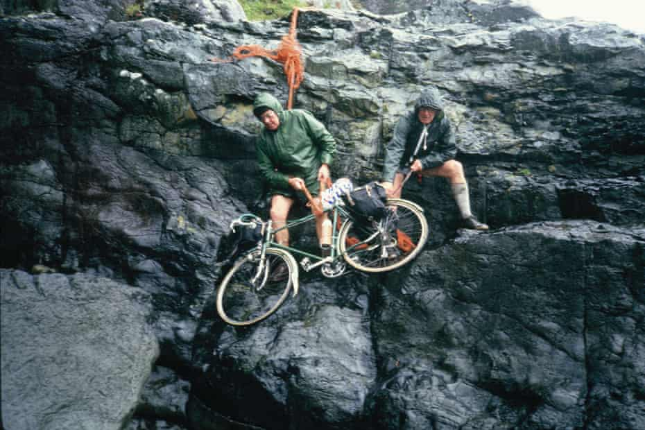 Two cyclists lower a bike down a rocky face.