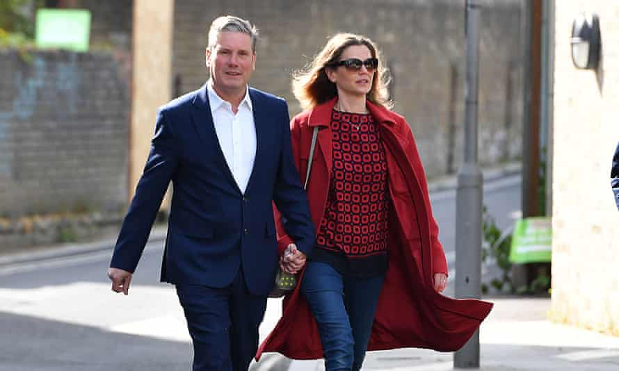 Keir and Victoria Starmer walking hand in hand along a street