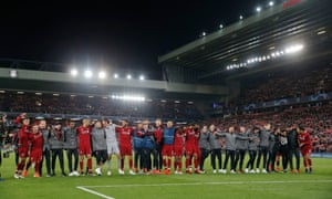 The Liverpool players and staff celebrate in front of the Kop