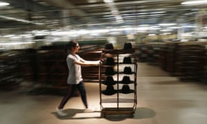 A worker pushes a cart with hats in Borsalino's hat factory, in Spinetta Marengo