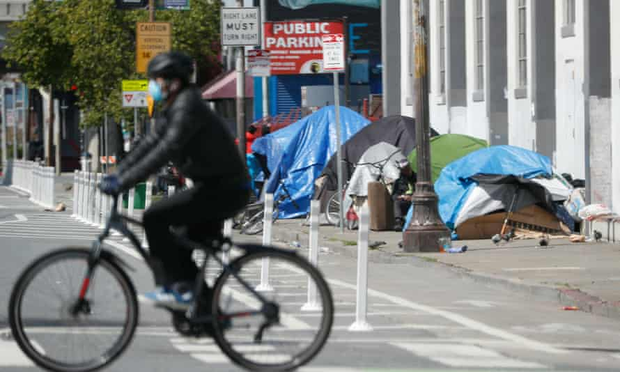 A cyclist rides past a homeless encampment along a sidewalk in San Francisco.