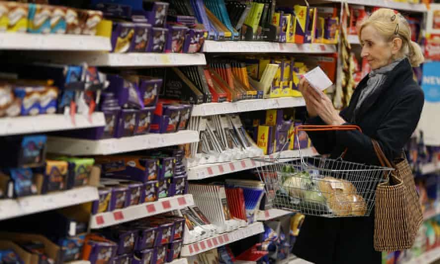 A shopper checks her shopping list in a supermarket.