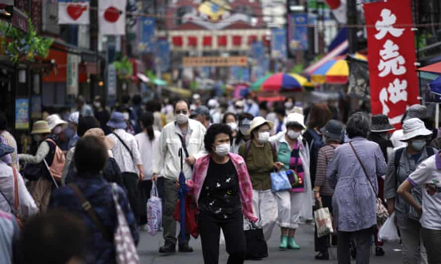 A street is crowded with  shoppers in Tokyo