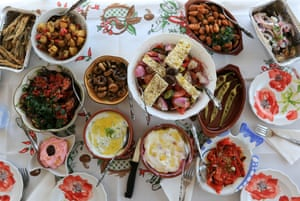 A greek meze, featuring vegetables, pulses and breaded fish