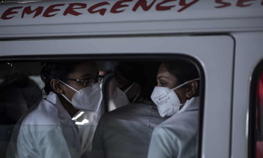 Health workers in Kerala leave in an ambulance