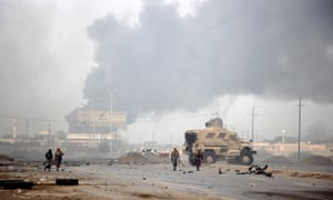 Yemeni government forces patrol as smoke billows from an alleged Houthi position.