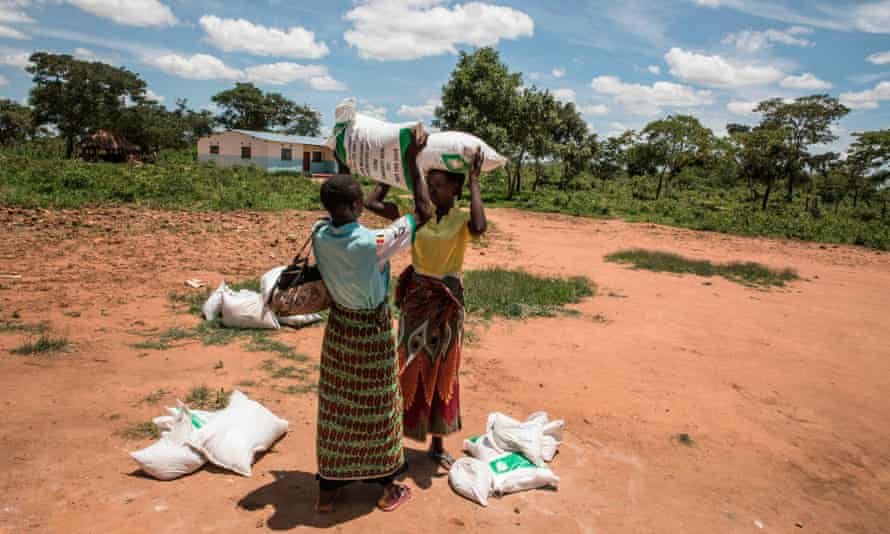 Two women help each other carry food bags at a distribution point in Simumbwe, Zimbabwe, January 2020.