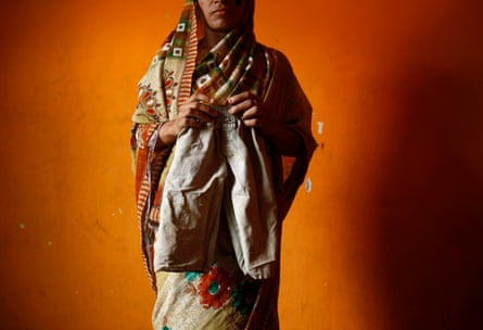 Chandravati poses with trousers belonging to her missing three-year-old daughter, Muskaan, inside her house in New Delhi.