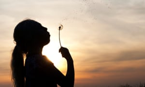 The silhouette of a young girl blowing a dandelion at dusk