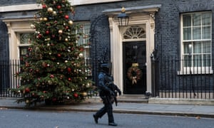 An armed police officer walks past Number 10 Downing Street