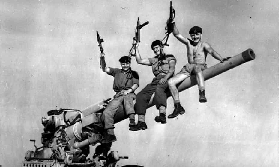 Three British soldiers sit triumphantly on a British-made gun they captured from Egyptian forces during the Suez crisis