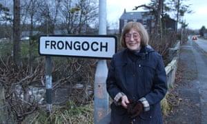 Val Mulkerns stands beside the village road sign