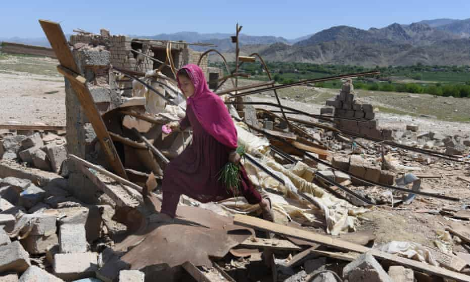 An Afghan girl walks amid the rubble of shops in Shadel Bazar after the US military dropped a GBU-43 Moab bomb in Achin district of Nangarhar province, Afghanistan.
