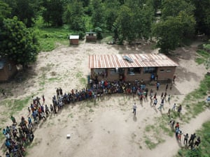 People in Tengani, Malawi gather to watch the drone taskforce of the inter-agency flood assessment team track the route of the storm, on 13 March