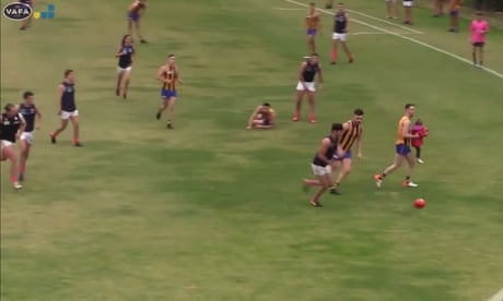 Toddler rescued by Aussie Rules player after running on to pitch during match – video