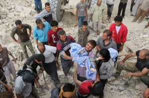Syrians pass the body of child after digging it out from under the rubble of a building