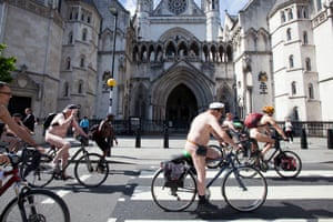 Participants cycle past The Royal Courts of Justice