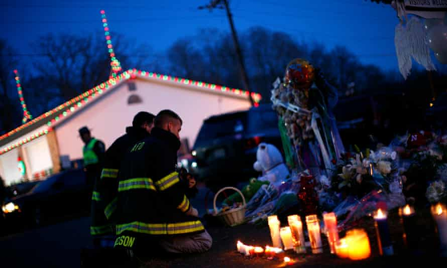 Firefighters kneel at a memorial at the Sandy Hook elementary school sign in Newtown, Connecticut.