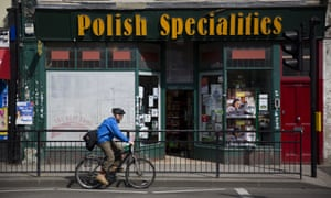 A man cycles past a Polish Specialities shop in London