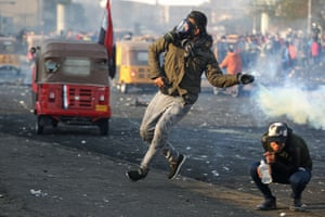 Baghdad, Iraq. An anti-government protester throws back a teargas canister at security forces during clashes at Tayaran Square, east of Tahrir Square in the centre of the Iraqi capital