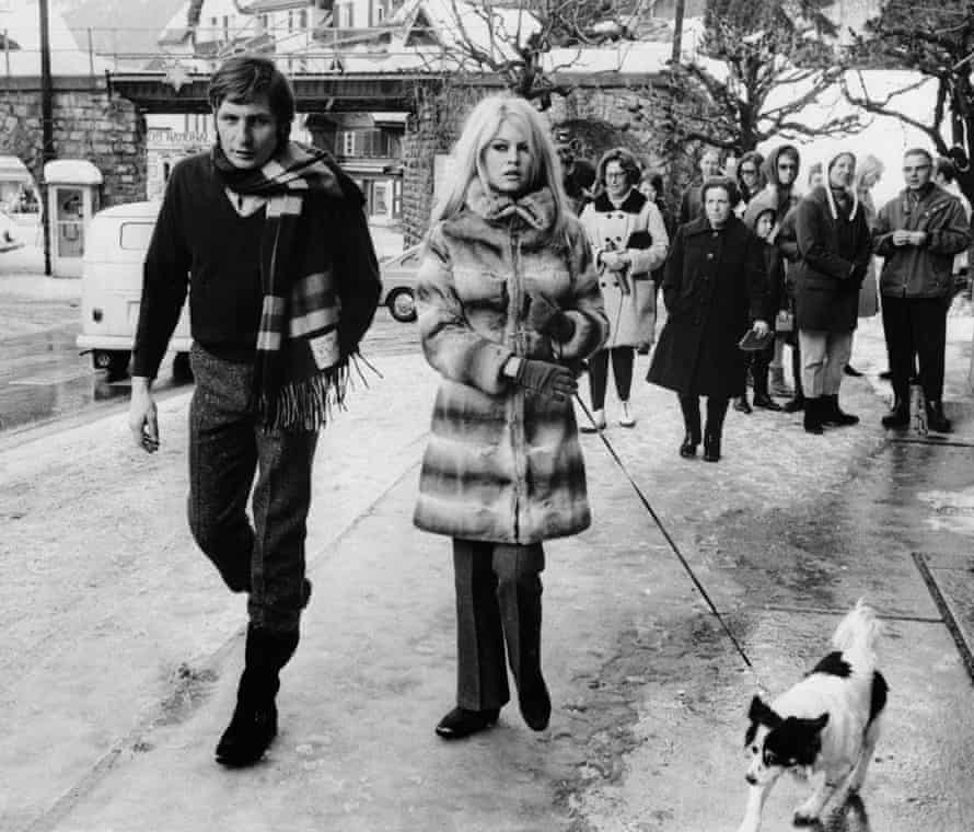 Brigitte Bardot her husband, Gunther Sachs, walk their dog through the streets of Gstaad in 1967.