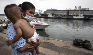 A woman wearing a mask holds her baby on the dock outside the MS Westerdam cruise ship docked in Sihanoukville, Cambodia