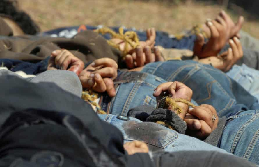 The bodies of 13 bullet-ridden men, with their hands tied behind their backs, victims of the drug war involving Guzmán's Sinaloa cartel, lie in a field.
