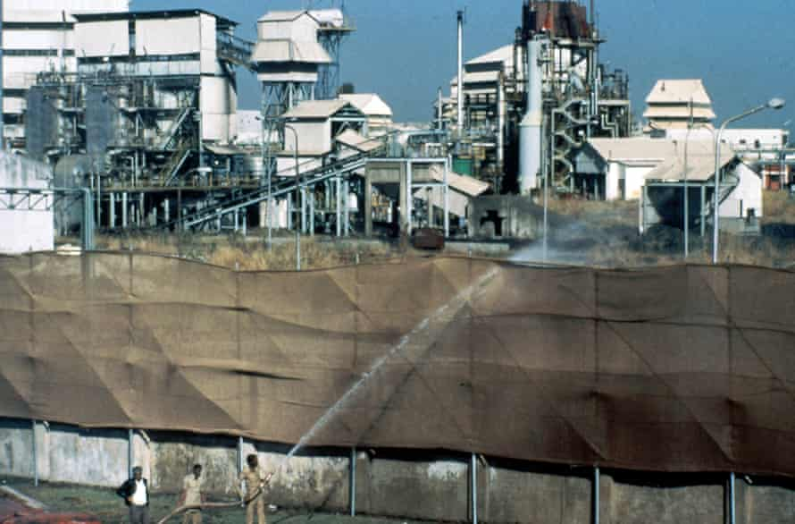 1984: Firemen hose water over canvas screens at factory boundaries to prevent the spread of dangerous fumes at the Union Carbide plant in Bhopal, India.