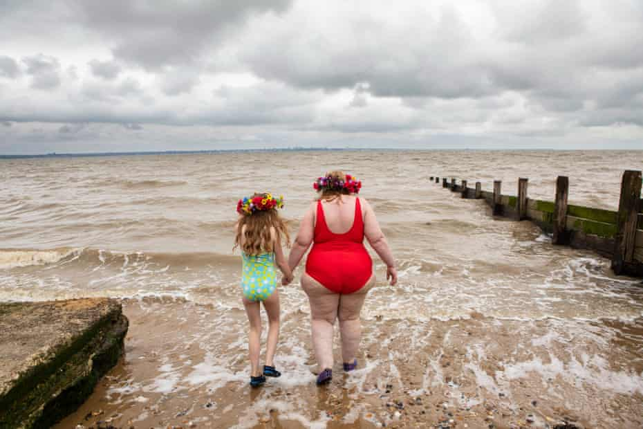 Anna Morell and her daughter Aurelia go into the water at All Hallows Beach in Kent.