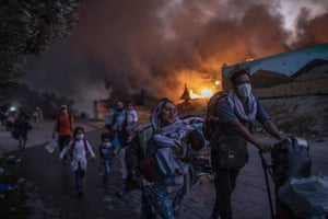 Refugees and migrants flee fire at the Moria camp on Lesbos in September. Successive fires made 12,000 inhabitants homeless (AP Photo/Petros Giannakouris)