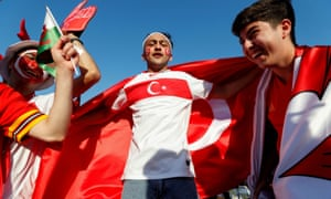 Fans carry flags and symbols of Switzerland, Wales and Turkey in central Baku.