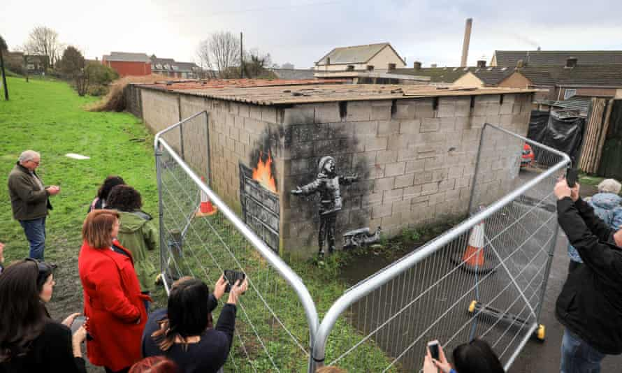 People gather to take picture of the Banksy in December