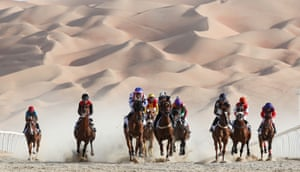 Jockeys compete in a race in the desert in the United Arab Emirates