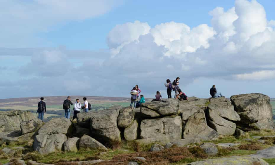 A group of young people standing on rocks on Ilkley Moor, Yorkshire on a sunny dayE8Y78T A group of young people standing on rocks on Ilkley Moor, Yorkshire on a sunny day