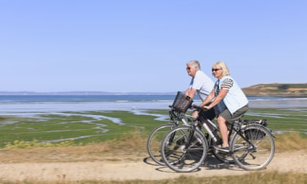 Middle aged /elderly couple on ebikes near the sea