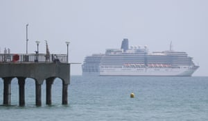 A fisherman fishes off of Boscombe pier in the shadow of the P&O cruise ship Arcadia.