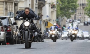 Tom Cruise on a motorbike speeds away from London police in a scene from Mission: Impossible – Fallout