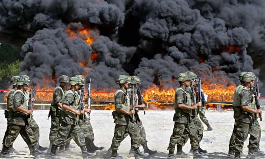 Mexican soldiers walk next to the site of the incineration of more than 20 tons of cocaine in Manzanillo.