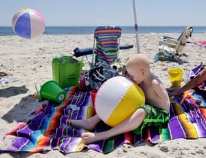 Mwigulu blows up a beach ball on a beach in New Jersey