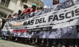 Pro-government supporters hold a banner during clashes between pro-government and opposition factions on the day of the sentencing of opposition leader Leopoldo López.