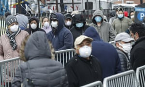 Patients wear personal protective equipment while maintaining physical distancing as they wait in line coronavirus tests at Elmhurst hospital center on Wednesday.