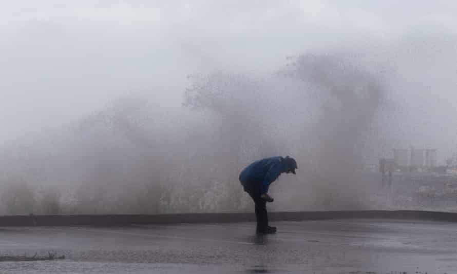 A reporter is splashed by waves as strong gusts of wind and bands of heavy rain hit the Jensen Beach Causeway Park in Jensen Beach, Florida on Tuesday.